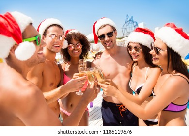 To the new year! Happy chilling youth on vacation, celebrating newyear in hot country, on resort, having white wine, cheering. Sun shines and reflects in spectacles, so shiny!