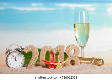 New Year inscription 2018, a bottle and a glass of champagne, clock and starfish on the sand.
