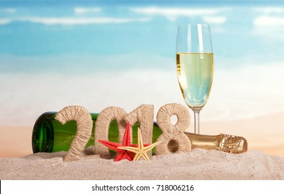 New Year inscription 2018, a bottle and a glass of champagne, starfish on the sand.