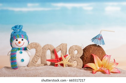 New Year inscription 2018, coconut with drinking straw and umbrella, snowman, flower, and starfish in the sand on the beach.