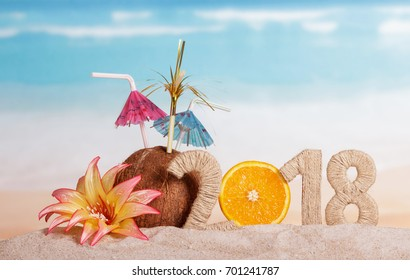 New Year inscription 2018, half of the orange instead of the numbers 0, coconut with straws and flower in the sand.