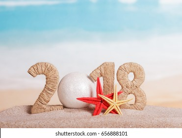 New Year inscription 2018, instead of the number 0 - white ball, starfish in the sand on the beach.