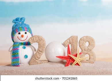 New Year inscription 2018, instead of the number 0 - white ball, snowman and starfish in the sand on the beach.