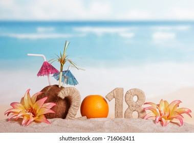 New Year inscription 2018, the orange instead of the numbers 0, coconut with straws and flowers in the sand.