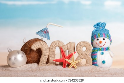 New Year inscription 2018, snowman and white Christmas ball, a coconut with a straw and umbrella, starfish on the sand.