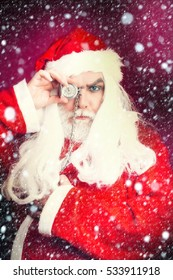 New year man with serious face has long white beard and hair in red santa claus christmas coat and hat holding clock on chain on studio background under snow and snowflakes