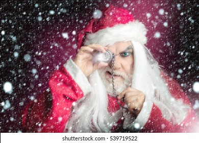New year man with serious face has long white beard and hair in red santa claus christmas coat and hat holding clock on chain on studio background
