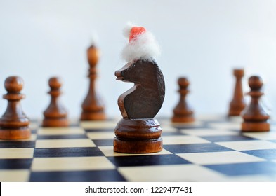 New Year on a chessboard, chess pieces in Santa's cap on a light background