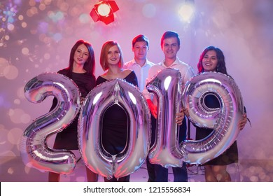 New Year party concept. Group of young friends holding silver colored numbers 2019 and throwing confetti