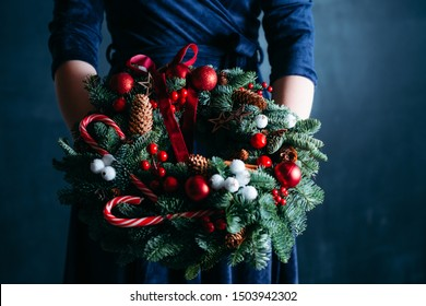 New year party gift. Cropped shot of woman in blue dress holding handmade Christmas wreath decorated with candy canes.