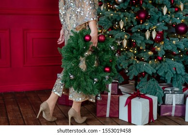 New year party gift. Cropped shot of woman in a gold dress holding handmade Christmas wreath on the background of the christmas tree and different gifts