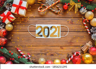 new year party preparation frame with gifts, present box, decoration, balls, fir tree, sparkles and cones on wooden background top veiw. Medical protective mask with gold numbers 2021 in the center