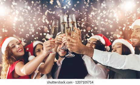 New Year party time. Multiethnic friends congratulating each other with holiday, toasting with champagne flutes