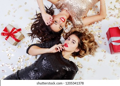 New  year party. Two elegant  gorgeous  celebrating women in trendy sequin dress lying on white floor with shining golden confetti and red gift boxes .
