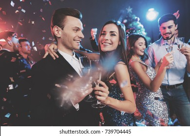 New Year party. Young couple dancing with glasses of champagne in hands. Against the background, young people's friends are dancing. Around fly confetti.