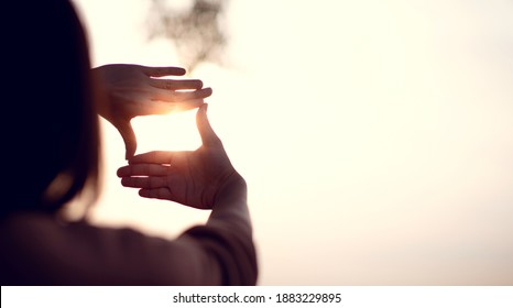 Neues Jahr Planung und Vision Konzept, Nahaufnahme von Frauen Hand Geste mit Sonnenuntergang, Frauen fangen den Sonnenaufgang. Kopienraum.