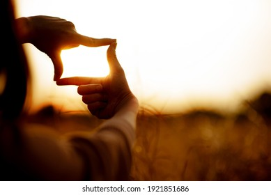 New year planning and vision concept, Close up of woman hands making frame gesture with sunset, Female capturing the sunrise.