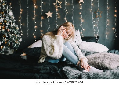 New Year portrait of a girl in festive interior. Christmas and  New Year concept. Young happy  woman in a cozy bed
