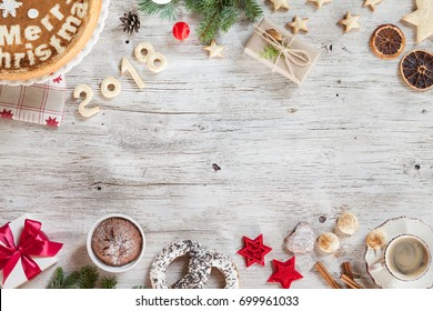 New year preparation concept. Christmass background with berries, cake, cup of coffee, red christmas tree toys. New Year composition candies, cinnamon, number year 2018 on a beige wooden background.