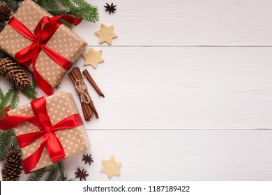 New Year presents with cookies and cinnamon on white wooden background, top view, copy space