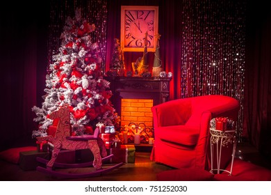 New Year. A red Christmas tree stands by the fireplace. New Year at the fireplace.
