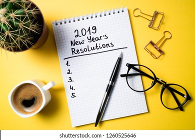 New year resolution 2019 on desk. 2019 goals list with notebook, coffee cup and glasses on yellow background. Top view