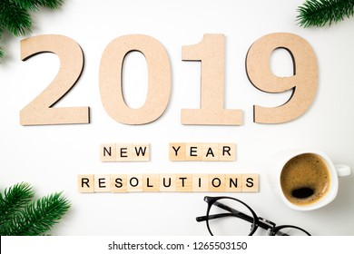 New year resolution 2019 on desk. 2019 goals, coffee cup, fir and glasses on white background. Goal, plan, strategy, change, idea concept. Top view