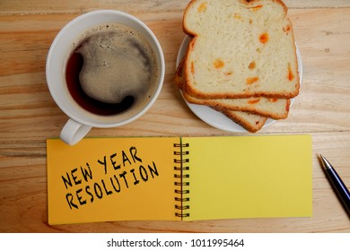 NEW YEAR RESOLUTION: Blank notepad and coffee cup on office wooden table