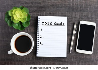 New Year Resolution Concept - 2020 Goals text on note pad with smart phone on top on desk