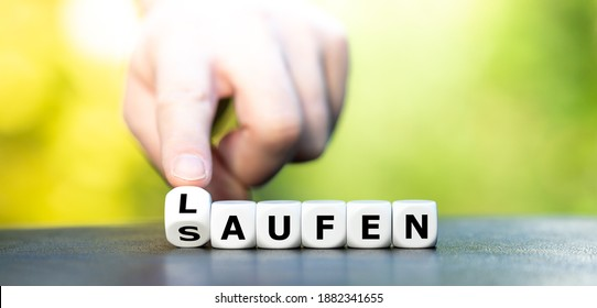 """New year resolution. Hand turns dice and changes the German word """"saufen"""" (booze) to """"laufen"""" (running)."""