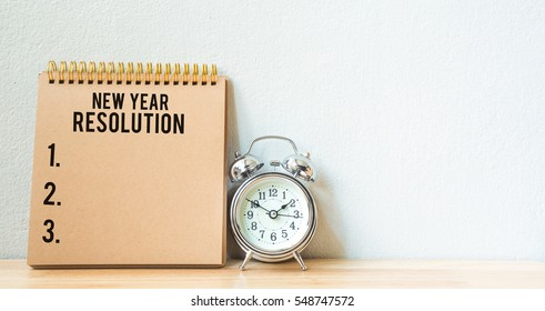 New year resolution on a notepad and alarm clock on wood table