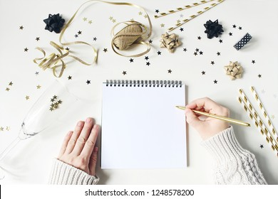 New Year resolution, wish list concept. Blank letter mock-up. Gold party decoration, confetti and wine glass on white table background. Flat lay, top view.