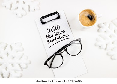 New year resolutions 2020 on desk. 2020 goals list with notebook, coffee cup and glasses on white background. Goals, plan, strategy, resolutions, change, idea concept