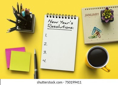 New Year resolutions, goals or action plan concept. Notebook on office table with calendar, coffee, plant and stationery. Flat lay (top view) notepad for input copy or text on yellow background.