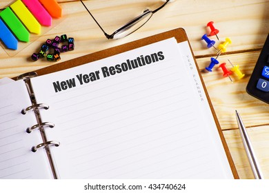 """""""New Year Resolutions"""" text on paper in open diary with spectacles, colourful push pin, pen and calculator on the wooden table"""