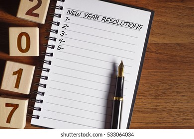 New year resolutions written on notebook with a pen and a wooden cube - 2017 concept with copy space