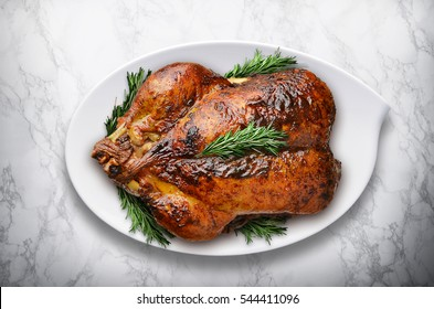 New Year roasted turkey with rosemary on white marble table.