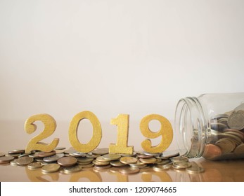 New year saving money and financial planning concept. Coins spilling out of glass bottle w/ gold wooden number 2019 on table. Idea for business growth, tax payment, investment and banking. Copy space.