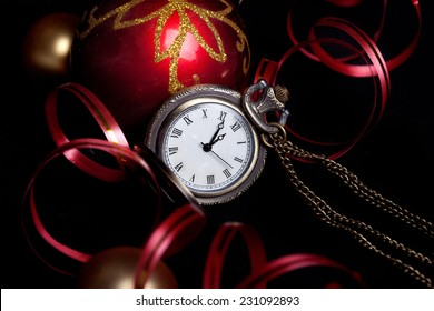 New Year set with watch and red and gold decoration baubles on black