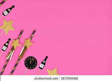 New Year Silvester celebration flat lay with golden, black and white striped paper stars and champaign flute and clock paper decoration on pink background with copy space