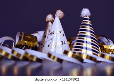 New Year silvester party hats and golden garland streamers on dark blue background