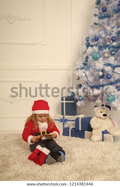 New year small boy at Christmas tree. Winter holiday and vacation. Santa claus kid with present box, black Friday. Christmas happy child with bear and gift, cyber monday. Xmas party celebration.