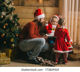 New year small girl and man, fairytale. Xmas celebration, fathers day. Christmas happy children and father read book. Santa claus kid and bearded man at Christmas tree. Winter holiday and vacation.
