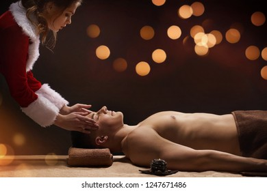New Year SPA concept. Beautiful Santa girl makes SPA treatment for young athletic man. Warm bokeh lights on background.