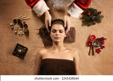 New Year SPA concept. Santa masseur make SPA treatment for young beautiful woman. New Year decoration, candles, warm inviting colors.