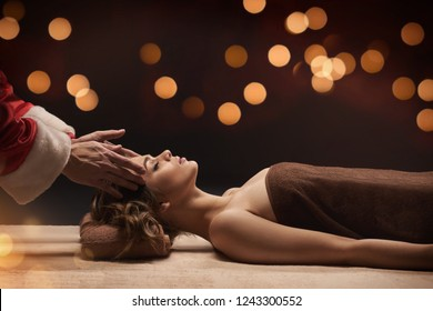 New Year SPA concept. Santa masseur make SPA treatment for young beautiful woman. Warm bokeh lights on background.