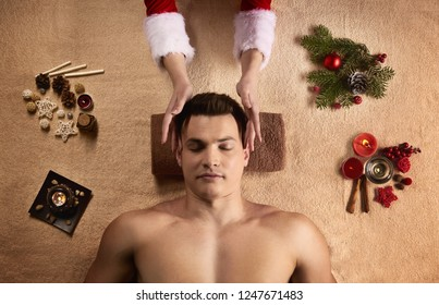 New Year SPA concept. Young athletic men getting SPA treatment with Santa girl.