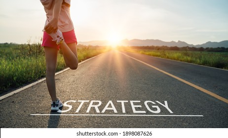 New year or start straight concept.word strategy written on the asphalt road and athlete woman runner stretching leg preparing for new year at sunset.Concept of challenge or career path and change