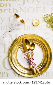 "New year table setting with exclusive and luxury golden cutlery, with decoration and christmas decor over a tabletop with celebrations world "" new year"" ,flat lay,top view"