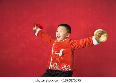The New Year themed boy wears traditional Han costume and plays cymbals